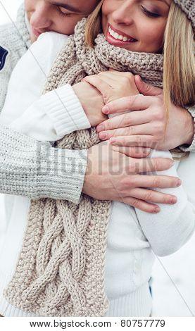 Tender man embracing happy girlfriend in winterwear