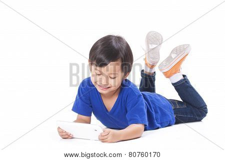 Cute boy using tablet while lying on the floor