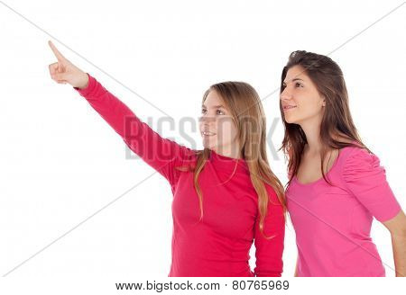 Two different sisters pointing something isolated on a white background