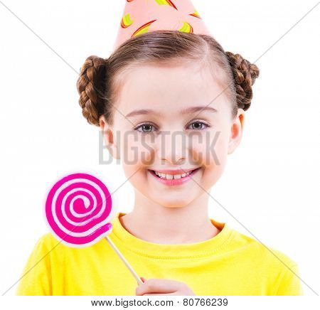 Happy little girl in yellow t-shirt and party hat holding colored candy - isolated on white.