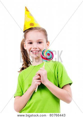 Portrait of smiling little girl in green t-shirt and party hat with colored candy - isolated on white.