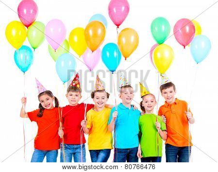 Group of smiling children in colored t-shirts and party hats with balloons on a white background.