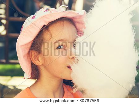 Cute girl with white cotton candy. Toned