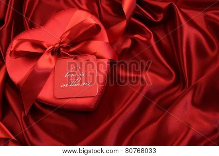 Chocolate box with gift card on satin background