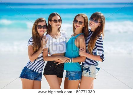 Beautiful girls are photographed on a tropical resort on the background of the beach and ocean.