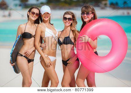 Four slender woman in a bikini with a lifeline near the ocean.
