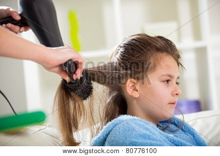 Mother dries hair to his daughter in the living room