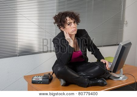 Young Woman Sitting In Lotus Yoga Pose On Desk In Office