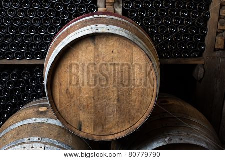 Oak Barrels With Wine Bottles