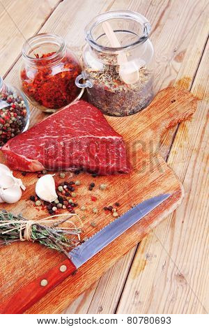 raw beef meat fillet with peppercorn and thyme and differnt spices in glass bottles ready to grill on wood figured aged board over table