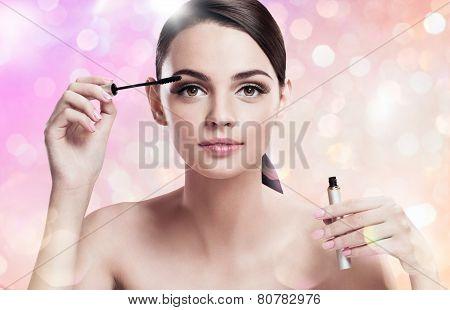 Charming young lady applying mascara