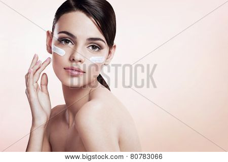 Skin care lady putting face cream