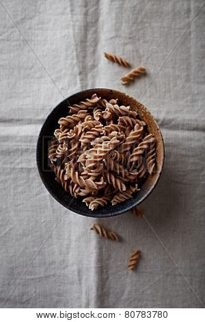 Wholegrain spelt pasta in a ceramic bowl (organic pasta)