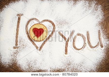 Heart and I Love You words of white flour on a wooden board. Cooking with love. Holiday backing background. Eco food and home cooking.