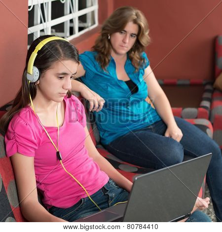 Sad and worried mother looks at her internet addicted teenage daughter