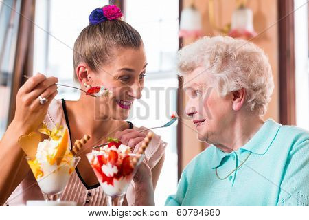 Senior woman and granddaughter having fun eating ice cream sundae in cafe