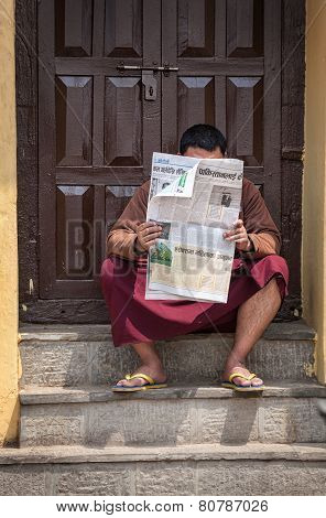 Buddhist Monk Reading Newspaper In Nepal