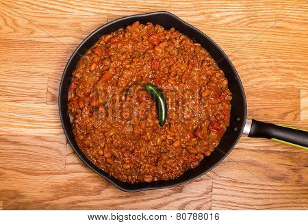Chili In Black Pan On Wood Table With Jalapeno Pepper
