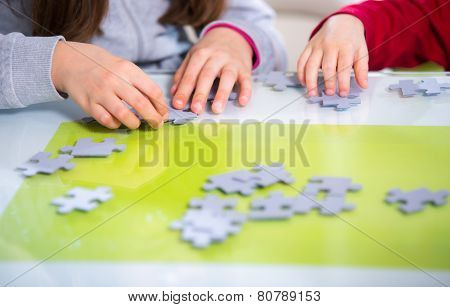 Two children playing with puzzles