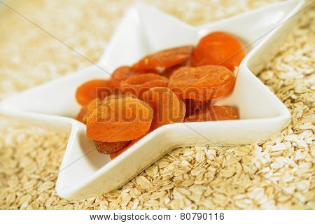 Dried apricots on the plate with oat flakes in the background