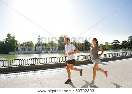 Runners jogging running in Madrid El Retiro city park. Exercising woman and man runner training on jog living healthy lifestyle in Buen Retiro Park, Parque el Retiro in Madrid, Spain, Europe.