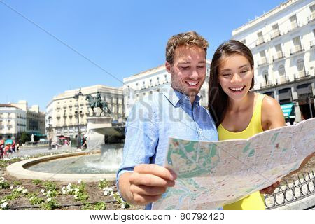 Tourists couple with map in Madrid. Sightseeing people looking at map for tourist attractions and famous landmarks while visiting Puerta del Sol in Madrid, Spain. Multiracial couple.