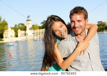 Romantic couple portrait embracing in love looking at camera. Multiracial woman and man smiling happy by lake in El Retiro in Madrid, Spain, Europe.