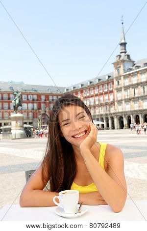 Woman portrait at cafe drinking coffee in Madrid, Spain on Plaza Mayor. Mixed race Asian Caucasian girl smiling happy at camera sitting at table.