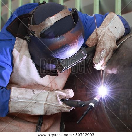 Welder is welding big column with mig method