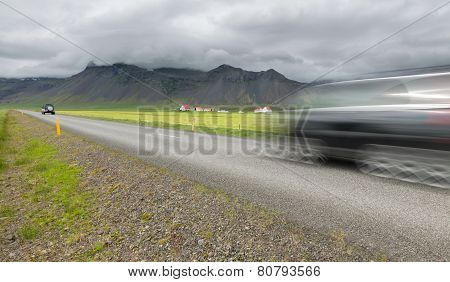 Iceland mountains with straight road and blurred car motion