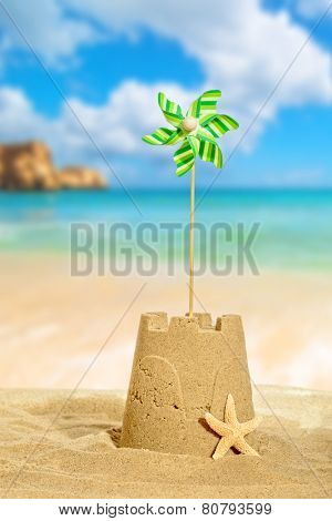 Sandcastle with pinwheel against a beach background