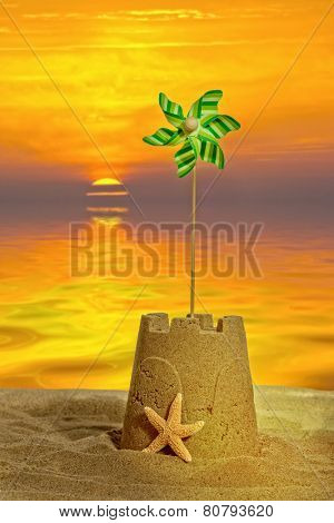 Sandcastle with windmill at sunset