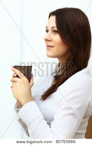 Businesswoman having a cup of coffee while reading an article on her tablet computer.