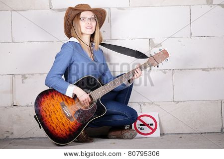 woman in a hat plays guitar