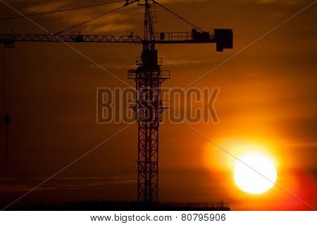 Silhouettes Of Construction Cranes Agains Sunrise