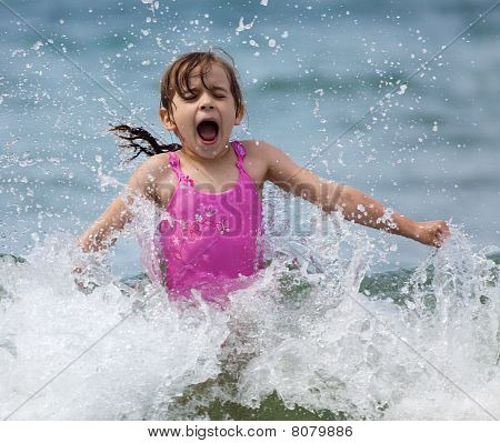 Little Girl Laughing And Crying In The Spray Of Waves