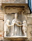 image of tithe  - Detail of a carving on a building in Venice Italy showing the Pope giving alms to the poor - JPG