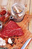 foto of flesh  - fresh raw beef meat fillet flesh with peppercorn and thyme ready to grill on wood figured old style board  over table with spices in glass - JPG