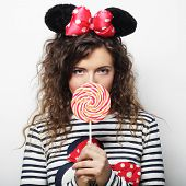 image of lolita  - young happy curly woman with mouse ears holding lollipop - JPG