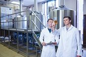 foto of beaker  - Two men in lab coat looking at the beaker with beer in the factory - JPG