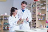 stock photo of prescription  - Trainee holding a prescription while talking to the pharmacist in the pharmacy - JPG