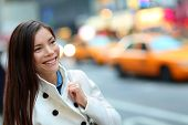 stock photo of cabs  - New York City Manhattan woman walking in street wearing coat downtown with yellow taxi cabs in background - JPG