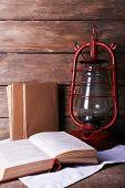 stock photo of kerosene lamp  - Kerosene lamp with books on rustic wooden background - JPG