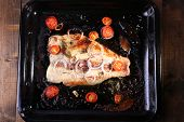 picture of pangasius  - Dish of Pangasius fillet with onion and cherry tomatoes on burn pan and wooden table background - JPG