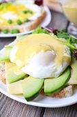 pic of benediction  - Toast with egg Benedict and avocado on plate on wooden table - JPG
