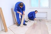 stock photo of floor covering  - Two men in laid wood floor in white room - JPG