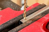 picture of drill bit  - A drill bit in a drill press. ** Note: Shallow depth of field - JPG