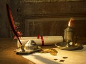 Постер, плакат: Antique parchment paper sheets lit by candlelight on a vintage colonial wood desk with ink writing f