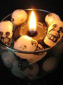 stock photo of magickal  - Closeup of black candle with wax skulls - JPG