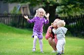 stock photo of leaf-blower  - Beautiful young mother with her daughter and son playing on grass - JPG